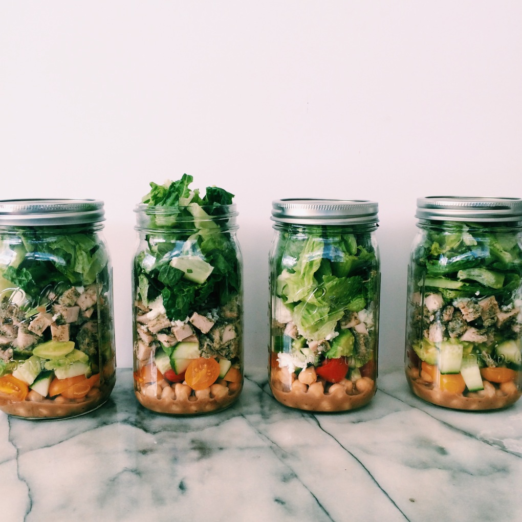 Salad in a jar with pesto chicken, garbanzo beans, cucumber, tomato, avocado, and feta cheese